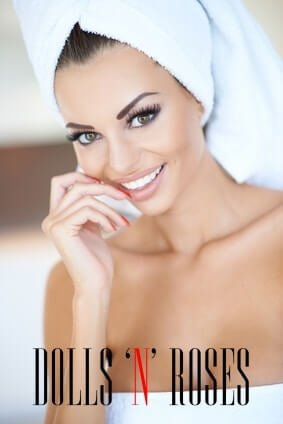 Beautiful tanned woman in a beauty portrait with her head and body wrapped in clean fresh white towels smiling as she waits in a spa or resort for a pampering rejuvenating treatment